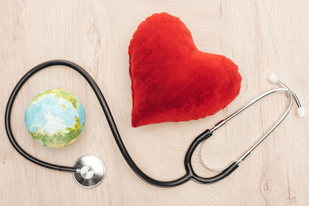 top view of bright toy heart and toy earth, stethoscope on wooden background Stock Photo