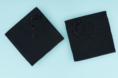 Top view of black academic caps isolated on blue