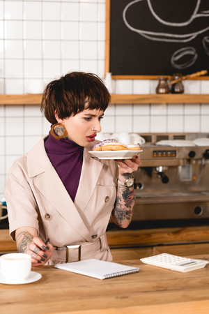 disgruntled businesswoman holding plate with macaroons while standing at bar counter in cafeteria