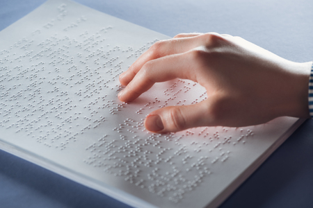 close up view of young woman reading braille text with hand Stock Photo