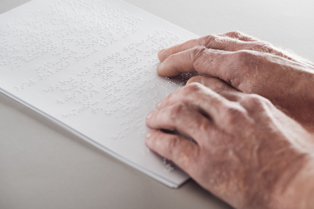 cropped view of senior man reading braille text isolated on grey