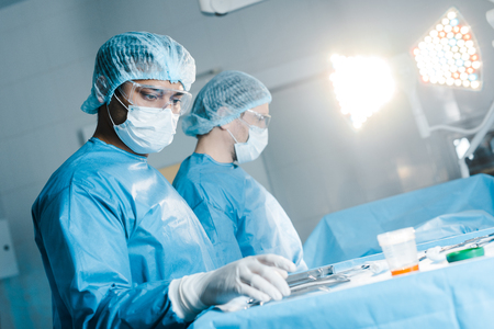 verpleegster en chirurg in uniform en medisch masker met medische apparatuur Stockfoto