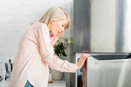 surprised blonde pregnant woman looking at fridge in kitchen