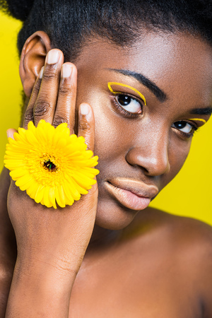 beautiful african american girl with flower looking at camera isolated on yellow