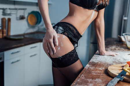 Partial view of sexy girl in black lingerie touching hip near wooden table in kitchen Stockfoto
