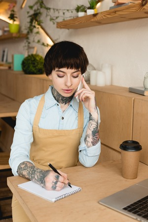 concentrated waitress talking on smartphone and writing in notebook