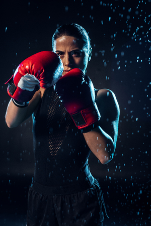 Concentrated boxer in red boxing gloves standing under water drops on black 版權商用圖片