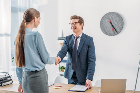 woman shaking hands with cheerful recruiter in glasses standing near table