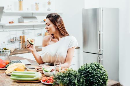 Pretty stylish girl holding cut avocado near table in kitchen