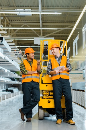 smiling multicultural workers talking while standing near scissor lift