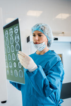 attractive doctor in medical cap and uniform holding x-ray in clinic Imagens