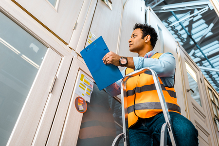 handsome, concentrated indian warehouse worker standing on ladder and holding clipboard Stock Photo