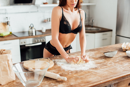 Partial view of sexy woman in black lingerie kneading dough in kitchen Stockfoto