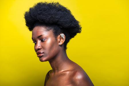 Nachdenkliche attraktive afroamerikanische Frau mit Ohrstulpe auf Gelb
