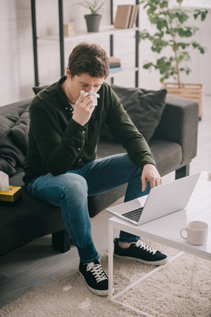 sick man sneezing in tissue while sitting on sofa and using laptop at home Banco de Imagens