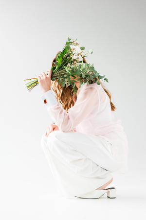 girl covering face with flowers with green eucalyptus leaves while sitting on white Reklamní fotografie