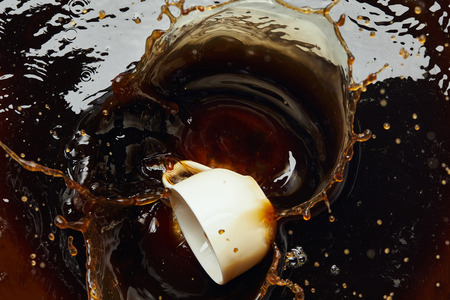Overturned white porcelain cup with black coffee and splash