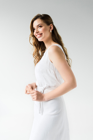 cheerful girl in dress smiling while standing on white