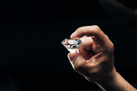 Teilansicht eines Mannes, der einen großen klaren, glänzenden Diamanten isoliert auf Schwarz hält