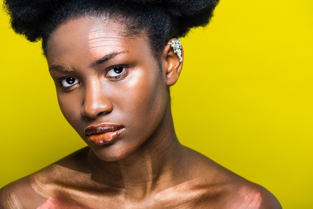 Pensive african american woman with ear cuff isolated on yellow