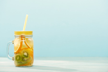 detox drink in jar with oranges, kiwi and straw isolated on blue
