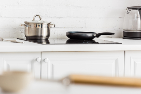 selective focus of stainless saucepan and black frying pan on electric stove in kitchen 版權商用圖片