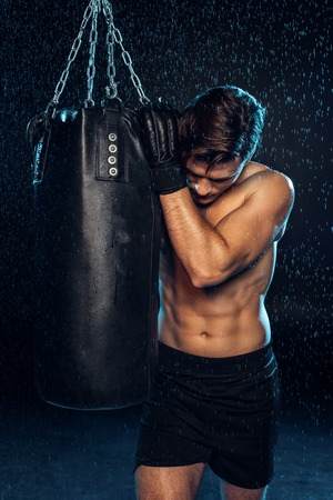 Exhausted boxer in black briefs holding punching bag and looking down on black 版權商用圖片