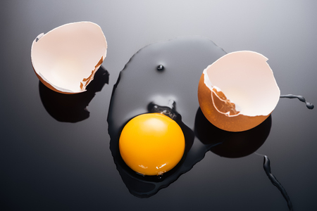 close up of fresh smashed egg with yolk, protein and eggshell on black background