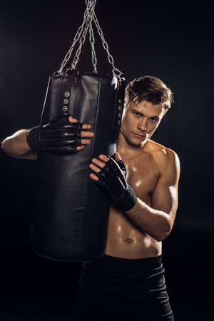 Serious boxer in gloves holding punching bag and looking at camera