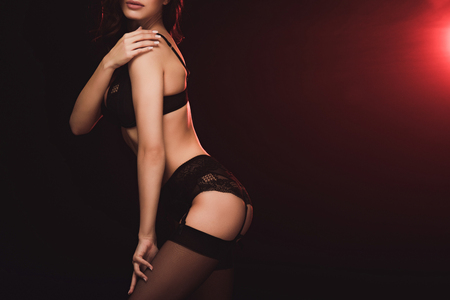 cropped view of woman in lace lingerie and stockings posing on black with red light and copy space Foto de archivo