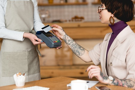 partial view of waitress holding payment terminal near businesswoman with credit card Stock Photo