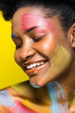 Mujer afroamericana con arte corporal sonriendo con los ojos cerrados aislados en amarillo