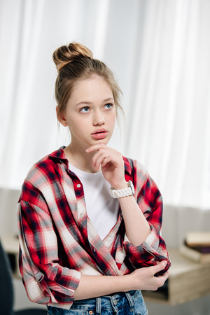 Pensive teenage kid in red checkered shirt looking away
