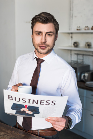 serious man holding business newspaper and coffee cup while looking at camera Banque d'images - 120926490