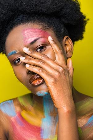 Hübsche Afroamerikanerin mit Körperkunst, die das Gesicht isoliert auf Gelb berührt