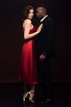 beautiful woman in fashionable red dress posing with african american man in suit isolated on black