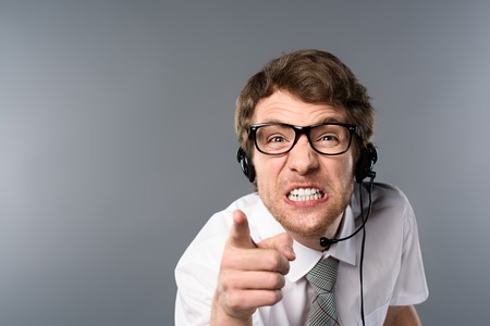 irritated call center operator in headset and glasses pointing with finger at camera