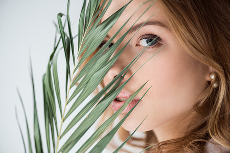 pretty woman looking at camera through palm leaf on white