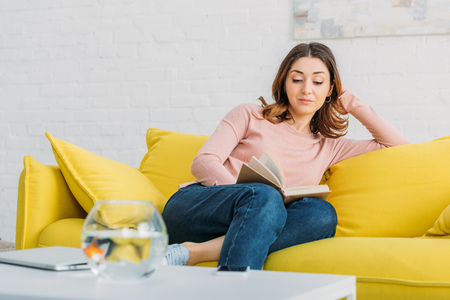 beautiful woman reading book while resting on yellow sofa at home Imagens