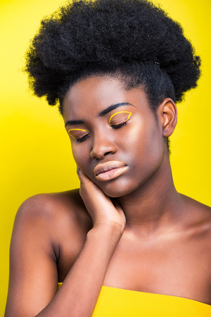 beautiful african american woman with closed eyes isolated on yellow Imagens