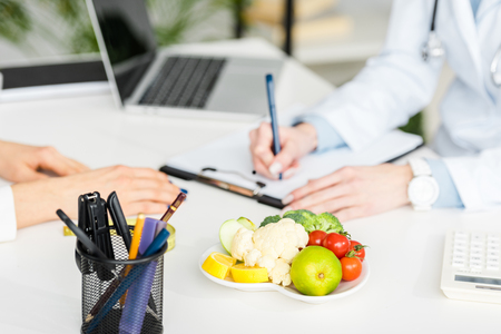 cropped view of nutritionist writing diagnosis near patient and plate with organic food