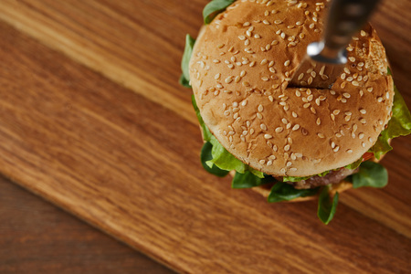 selective focus of knife in delicious burger on wooden chopping board