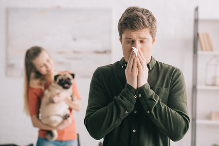 selective focus of man sneezing in tissue with closed eyes while standing near woman with dog