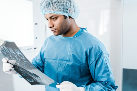 handsome doctor in medical cap and latex gloves holding and looking at x-ray