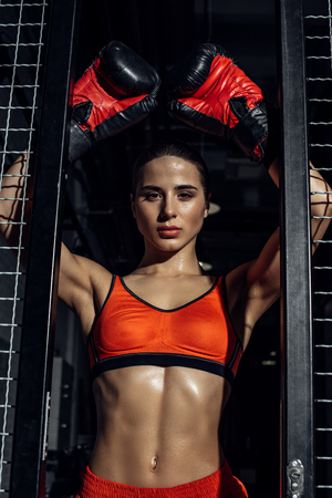 Attractive boxer standing with hands up near wire netting and looking at camera