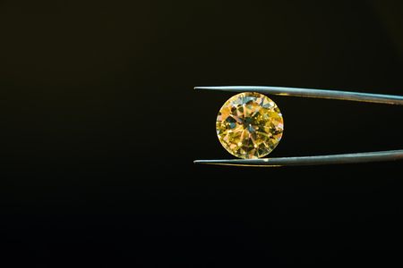 colorful yellow sparkling diamond in tweezers isolated on black Stock Photo