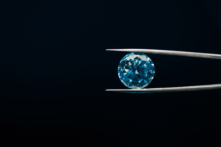 colorful blue sparkling diamond in tweezers isolated on black