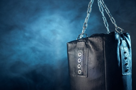 Leather punching bag hanging on steel chains on dark