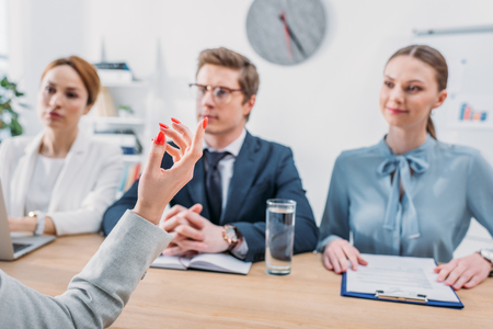 selective focus of female hand gesturing near recruiters during job interview Imagens