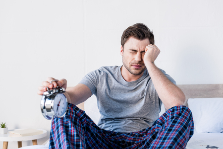 selective focus of handsome overslept man with closed eyes holding alarm clock Stock Photo